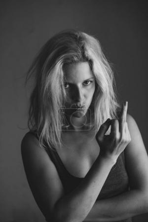 Photo for Woman showing flip off hand sign  and grimcing - Royalty Free Image