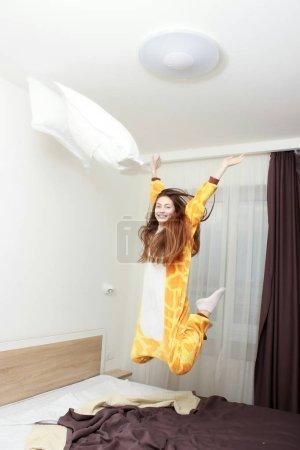 Funny girl in kigurumi pajamas jumping on the bed