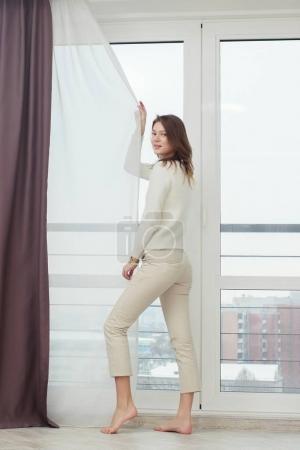 Photo pour Belle femme est réveillée et debout devant la fenêtre. Fille ouverture rideaux réunion lever du soleil - image libre de droit
