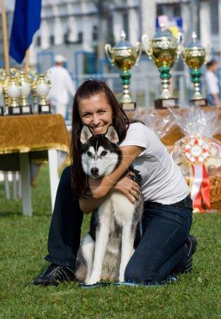 Photo pour Joyeuse propriétaire embrassant son husky frère à l'exposition canine - image libre de droit