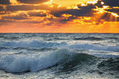 Beautiful sunrise with dramatic cloudscape over the ocean waves