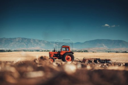 Photo for Farmer in tractor preparing land with seedbed cultivator, sunset shot - Royalty Free Image