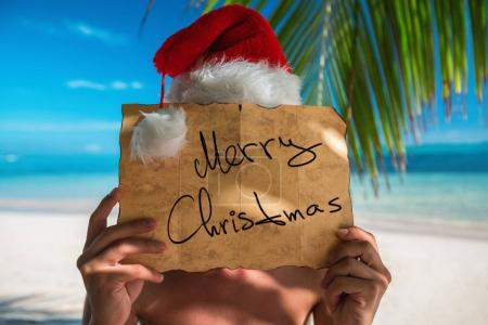 Photo for Tourist man with Santa Claus hat relaxing on tropical island beach. Punta Cana, Dominican Republic. - Royalty Free Image
