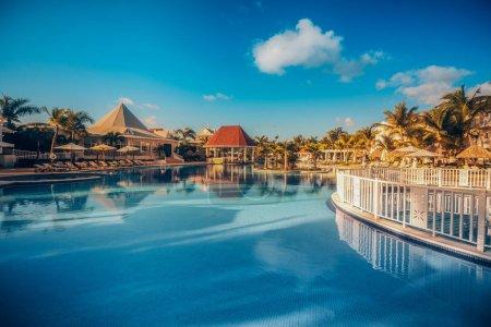 Photo pour Piscine tropicale et palmiers dans un complexe de luxe - image libre de droit