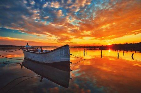 Mały dok i łódź nad jeziorem, zachód słońca