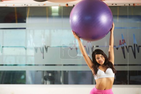 Woman holding fitness ball in modern gym backgroun...