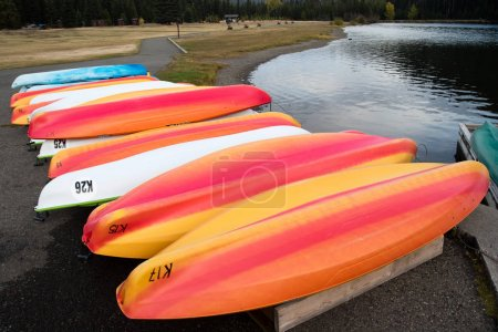 Colorful kayaks on a lake shore