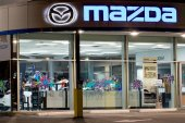 Vancouver. Canada - January 9, 2018: Mazda logo on the facade of official dealer office. Mazda Motor Corporation is a Japanese car brand, automotive manufacturer. Night shot with logos illuminated.