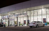 Vancouver BC, Canada - January 9, 2018: Office of official dealer BMW. BMW is a German automobile manufacturer specializing in high-performance and luxury cars. Night shot all is illuminated.