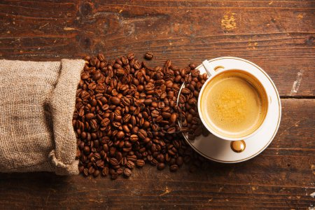 Photo for Coffee cup and beans on old wooden background - Royalty Free Image