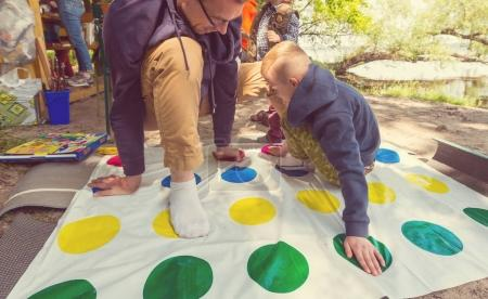 Kid and adult playing twister game outdoors