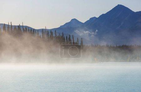 Photo pour Lac de montagne brumeux tôt le matin serein dans les montagnes. - image libre de droit