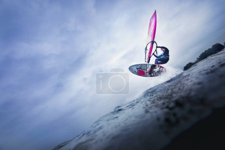 Photo for Airtime of windsurfer jumping over big wave balancing in sky - Royalty Free Image