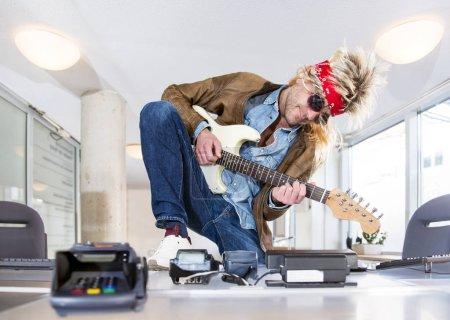 Photo pour Rockstar à une billetterie, jouer de la guitare, vente de billets pour un événement rock ou un concert au théâtre - image libre de droit