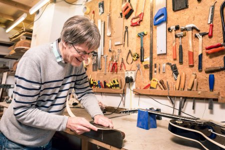 Smiling musical instrument maker working