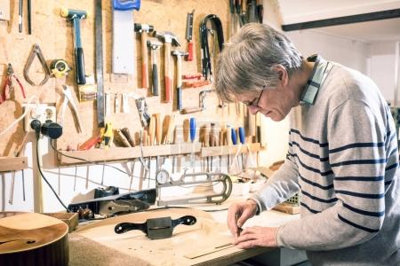 Luthier drawing the outline of a lute piece