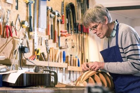 Instrument maker carving the body of a lute