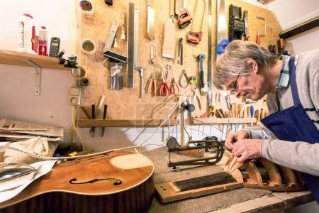 Luthier concentrating on carving a lute