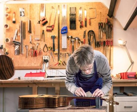 Craftsman in his workshop leveling the frets of a guitar