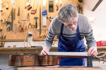 Man measuring the neck of a guitar
