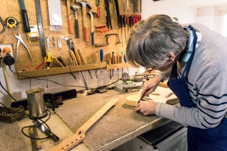 Luthier filing the neckpocket of an electric guitar
