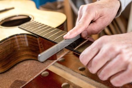 craftsman's hands, filing the frets of a guitar