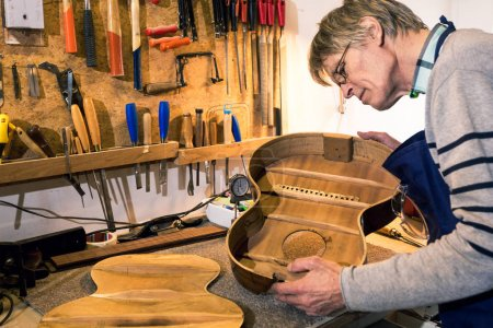 Luthier checking the body of an acoustic guitar