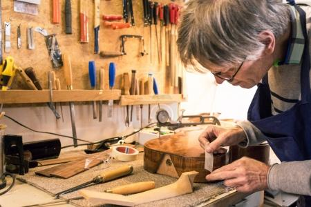 Instrument maker masking a guitar  with tape