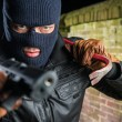 Gangster Holding Crowbar While Pointing With Gun A...