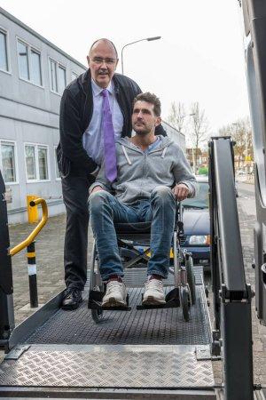 driver helping man on wheelchair