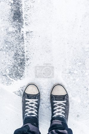 Photo for Worn sneakers on grunge pavement as copy space - Royalty Free Image