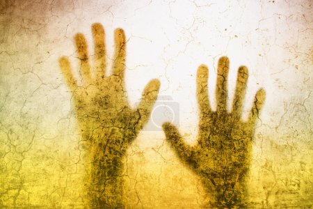 Back lit silhouette of trapped person hands behind matte glass