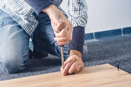 Photo pour Montage de meubles à la maison sur le plancher de l'homme, à la main avec tournevis - image libre de droit