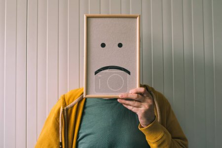Photo for Put a sad pessimistic face on, sadness and depressive emotions concept, man holding picture frame with smiley emoticon printed - Royalty Free Image