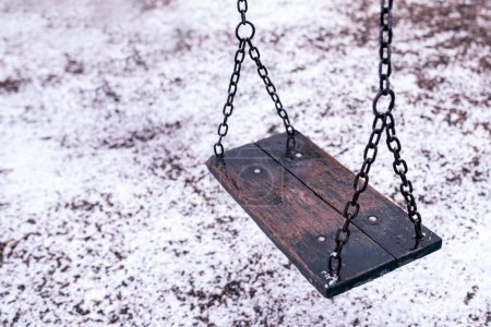 Empty swing on children playground under snow