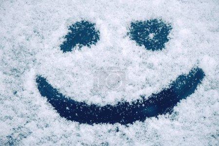 Foto de Carita feliz de emoticono en nieve, concepto de alegría y felicidad de temporada invierno - Imagen libre de derechos
