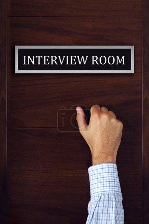 Businessman knocking on interview room door