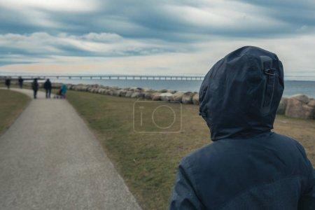 Persona femenina con capucha solitaria por detrás de pie en la orilla del mar