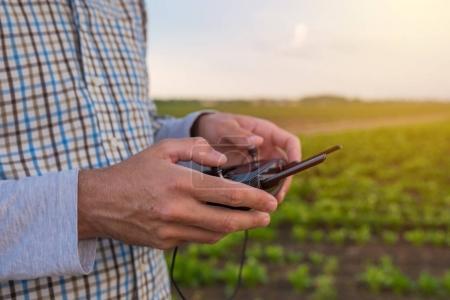 Hands of farmer using drone remote control