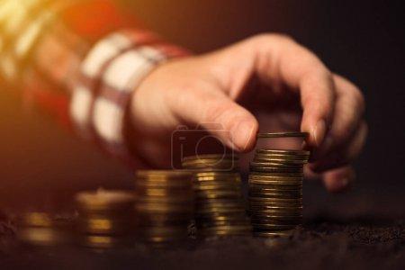 Photo pour Agriculteur, empilement de pièces de monnaie, profit et les revenus agricoles augmentent - image libre de droit