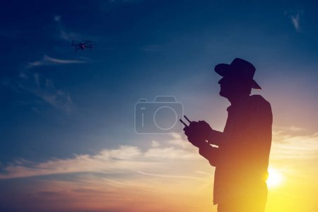 Silhouette of farmer using drone remote control