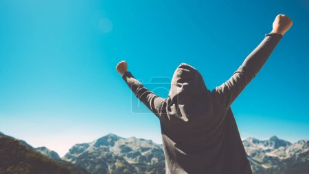 Photo for Winning and success. Victorious female person standing on mountain top with arms raised in V. Achievement and accomplishment in life. Toned image. - Royalty Free Image