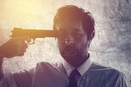 Businessman points gun to his head