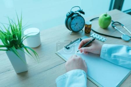 Photo pour Médecin généraliste écrivant des notes pendant l'examen médical, la médecine sur ordonnance et les soins de santé, image tonique bleue - image libre de droit