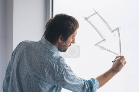 Photo for Businessman drawing arrow pointing down, conceptual symbol for profit loss and failure in business entrepreneurship - Royalty Free Image