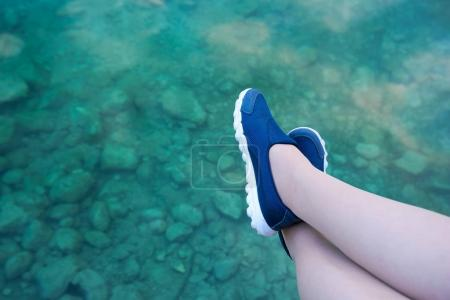 Photo for Relaxing feet by the lake. Woman sitting and resting outdoors on the bank of standing water. - Royalty Free Image