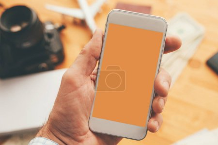 Photo for Travel app for mobile phone mock up screen, overhead view of male hand using smartphone with blank screen as copy space - Royalty Free Image