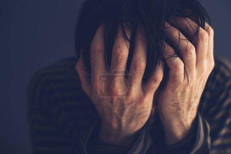 Photo pour Désespéré toxicomane tenant la tête, portrait discret avec un accent sélectif - image libre de droit