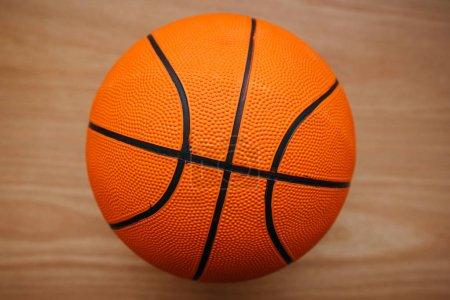 Photo pour Ballon de basket-ball portant sur le parquet de la Cour, vue de dessus - image libre de droit
