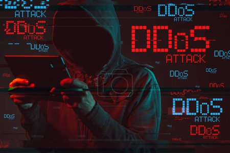 Photo for Distributed denial of service or DDoS attack concept with faceless hooded male person using tablet computer, low key red and blue lit image and digital glitch effect - Royalty Free Image